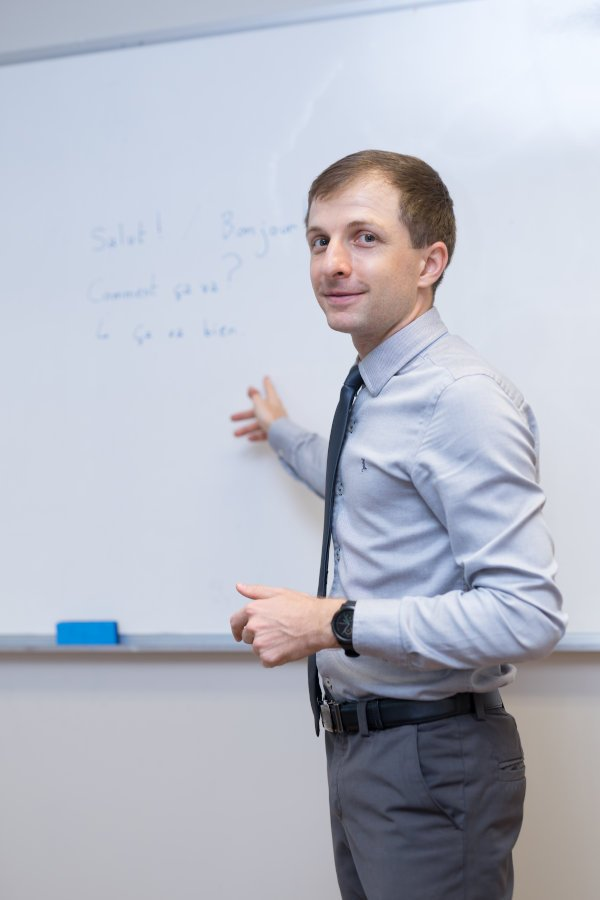 a French teacher in front of a whiteboard